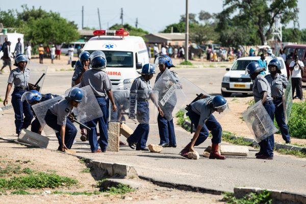 Police officers make way for an ambulance by removing stones from a barricade during a demonstration against the doubling of fuel prices on Jan. 14, 2019, in Bulawayo, Zimbabwe. (Zinyange Auntony/AFP/Getty Images)