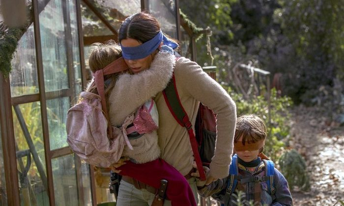 "Sandra Bullock in a scene from the film, ""Bird Box."" Netflix's post-apocalyptic survival film is drawing criticism for using footage of a real fiery train disaster but the streaming giant has no plans to remove it. (Saeed Adyani/Netflix via AP)"