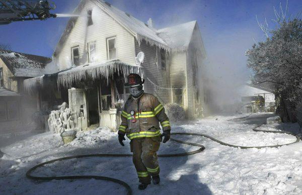 firefighter walks past home
