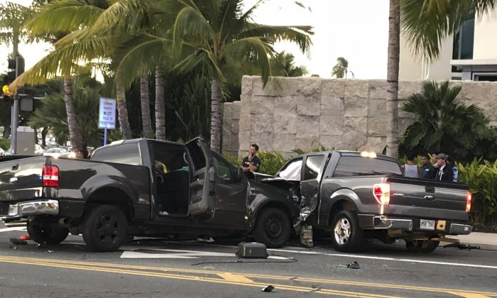 In this photo taken Monday, Jan. 28, 2019, is the scene of a multiple vehicle accident involving two trucks and a bicyclist in Honolulu. (Cindy Ellen Russell/Honolulu Star-Advertiser via AP)