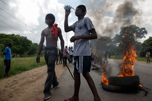 Men stand next to burning tyres as angry demonstrators protests fuel price hikes barricade the main route to Zimbabwe's capital Harare from Epworth township on Jan. 14, 2019. (Jekesai Njikizana/AFP/Getty Images)