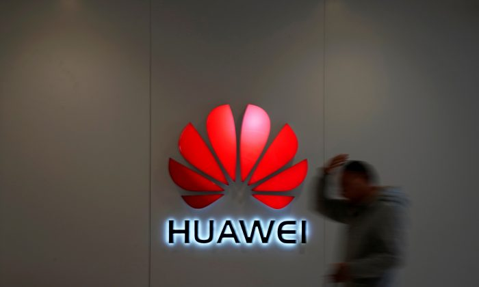 A man walks by a Huawei logo at a shopping mall in Shanghai, China on Dec. 6, 2018. (Aly Song/Reuters)