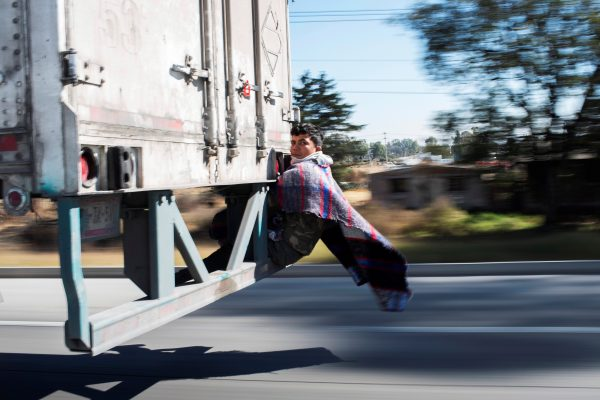 Migrant Javier Gomez, from Honduras, takes a lift in the back of a truck during his journey towards the United States, in Mexico City
