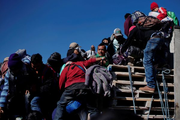 Migrants climb the back of a truck during their journey towards the United States, in Mexico City