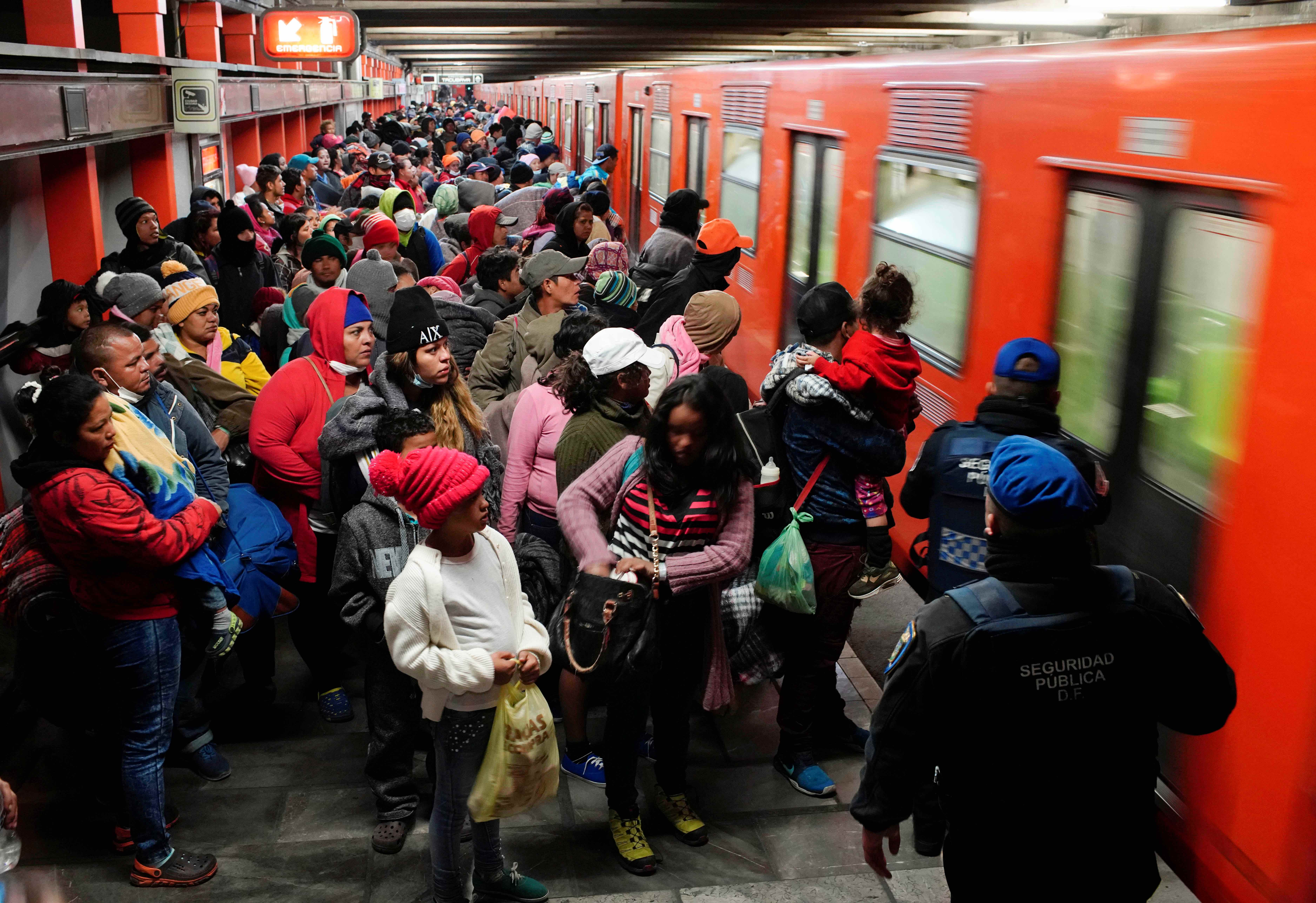 Migrants prepare to get into a train at an underground station during their journey towards the United States, in Mexico City