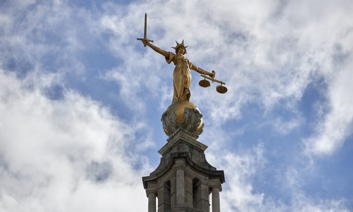 The 'Lady of Justice,' a 12-foot high, gold leaf statue on top of the dome of the Central Criminal Court, commonly referred to as The Old Bailey, in central London on Aug. 21, 2016. (Niklas Halle'n/AFP/Getty Images)