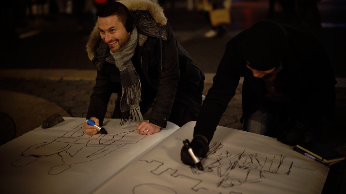 "One of the artists in the ""Sketchbook Vol. 1"" exhibition, Nicholas Sanchez participates in the giant sketchbook drawing competition in Union Square, New York on January 18. (Paul-Emile Cendron/Sugarlift)."