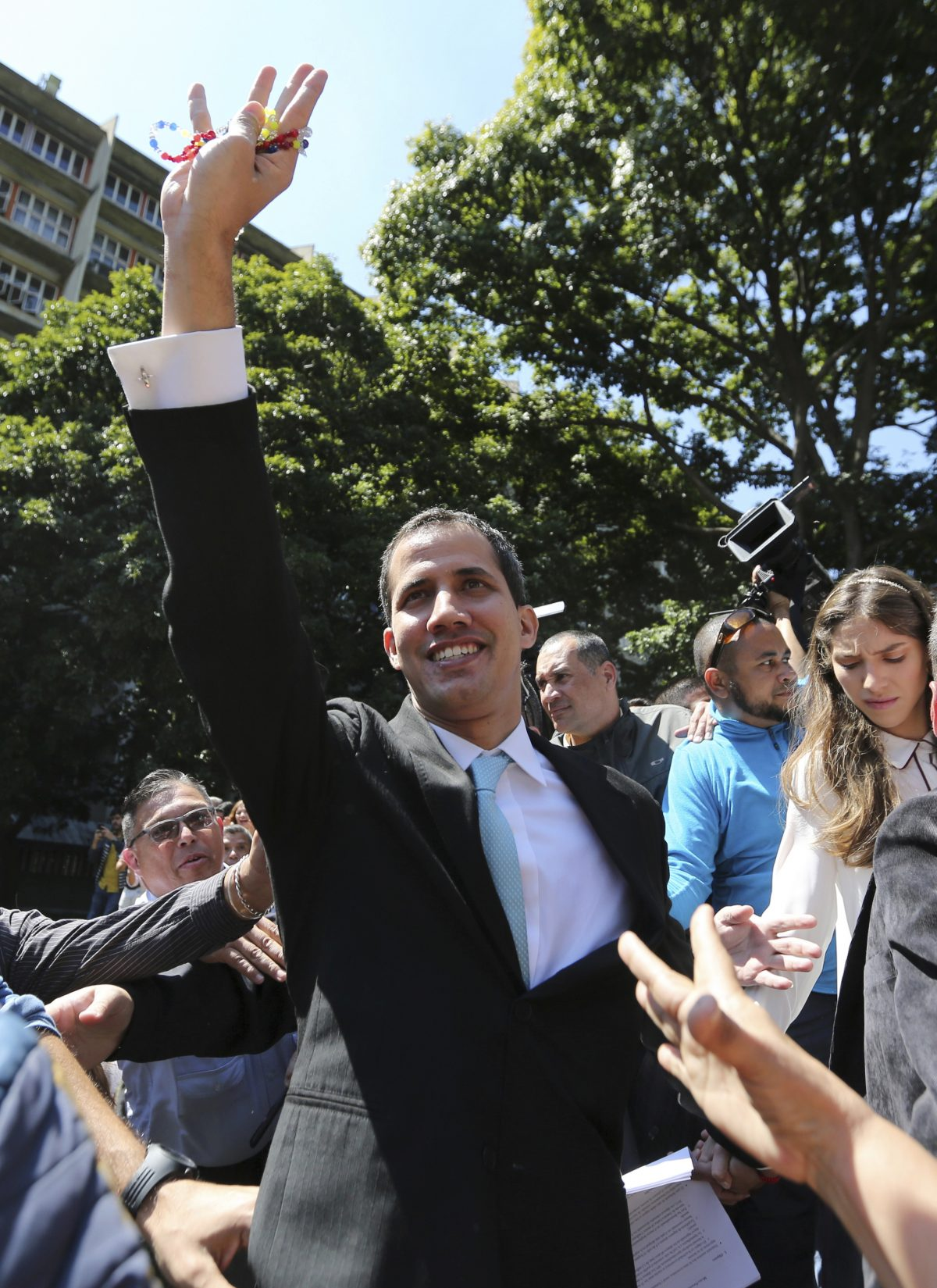 """Opposition National Assembly President Juan Guaido greets supporters upon his arrival to the Venezuelan Central University for a conference on economic plans for reviving the country in Caracas, Venezuela, Thursday, Jan. 31, 2019. An independent U.N. human rights monitor says economic sanctions are compounding a """"grave crisis"""" in Venezuela. (AP/Fernando Llano)"""