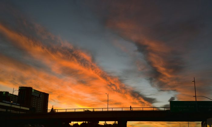 A pedestrian makes their way across an overpass under a dramatic sunrise during the early morning commute in Los Angeles on , on Feb. 1, 2019.  (AP Photo/Richard Vogel)