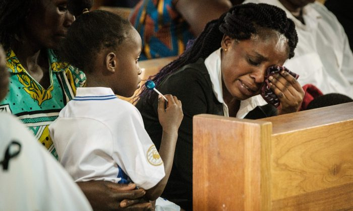 The wife of a staff member at the DusitD2 hotel cries next to one of her children during a memorial service on Jan. 23, 2019, for six staff members of the hotel who were killed during an attack at the Consolata Shrine in Nairobi, Kenya. (Yasuyoshi Chiba/AFP/Getty Images)