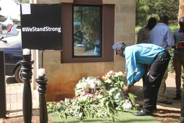 A security guard at 14 Riverside complex places flowers as memorial for the victims who perished during the attack on Dusit D2 Hotel and the 14 Riverside complex that took place in Nairobi, on Jan. 15, 2019. (Dominic Kirui for The Epoch Times)