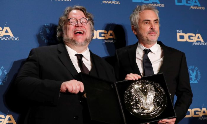 "Alfonso Cuaron (R), director of ""Roma"" holds his medallion as he poses with Guillermo del Toro after winning the Feature Film category at the Directors Guild Awards in Los Angeles, Calif., on Feb. 2, 2019. (Reuters/Mario Anzuoni)"