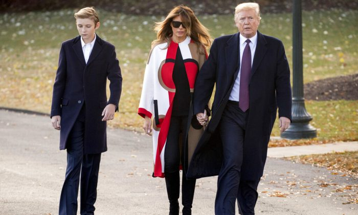 In this Nov. 20, 2018, file photo President Donald Trump accompanied by first lady Melania Trump, and their son Barron, left, walks towards Marine One on the South Lawn of the White House in Washington. (AP Photo/Andrew Harnik, File)