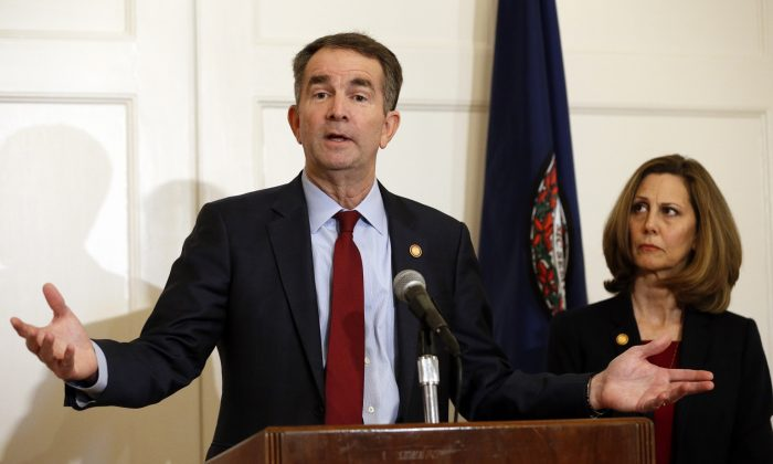 Virginia Gov. Ralph Northam, left, accompanied by his wife, Pam, speaks during a news conference in the Governor's Mansion in Richmond, Va., on Feb. 2, 2019. (AP Photo/Steve Helber)