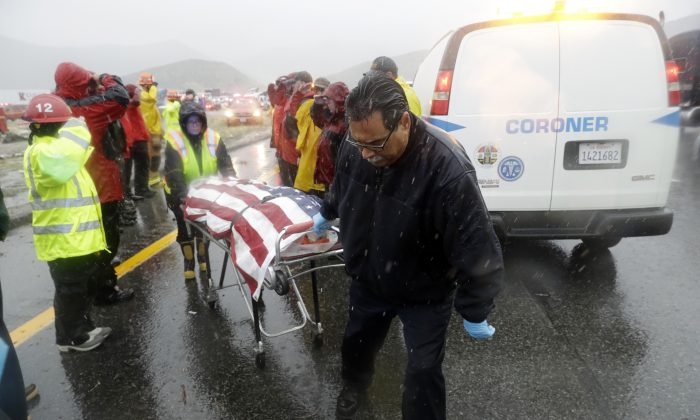 The flag-draped body of a volunteer member with the Ventura County search and rescue team, killed in a traffic accident, is loaded onto a coroner van as law enforcement personnel salute along Interstate Highway 5 south of Pyramid Lake, Calif., on Feb. 2, 2019. (Marcio Jose Sanchez/AP)