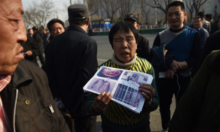 A petitioner holds photos of evidence in her grievance against local officials, outside a government petition office in Beijing on March 2, 2016. (Greg Baker/AFP/Getty Images)