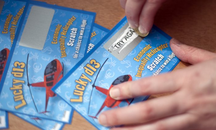 A woman scratches a lottery ticket 2 in Kassel, central Germany on June 8, 2012.(Barbara Sax/AFP/GettyImages)