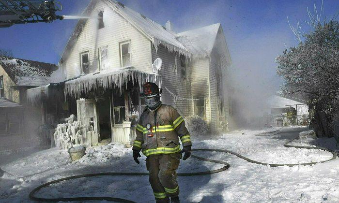 A firefighter walks past an ice-encrusted home after an early morning house fire in St. Paul, Minn., on Jan 30, 2019.  (Jean Pieri/Pioneer Press via AP, File)
