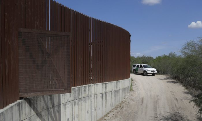 A U.S. Customs and Border Patrol vehicle passes along a section of border levee wall in Hidalgo, Texas, on Aug. 11, 2017. (Eric Gay, AP Photo/File)