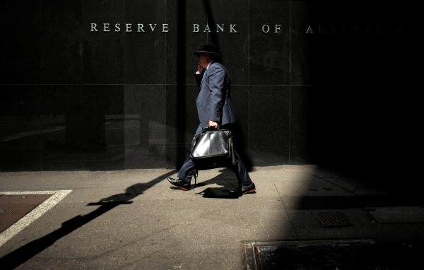 A Sydney businessman walks into the light outside the Reserve Bank of Australia