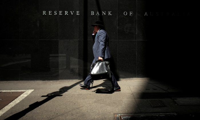 A Sydney businessman walks into the light outside the Reserve Bank of Australia (RBA), Feb. 3, 2015. (Jason Reed/Reuters)