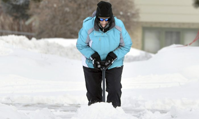 Florence Leingang clears the sidewalk of snow in front of her home in Mandan, N.D., on Feb. 4, 2019. (Mike McCleary/The Bismarck Tribune via AP)
