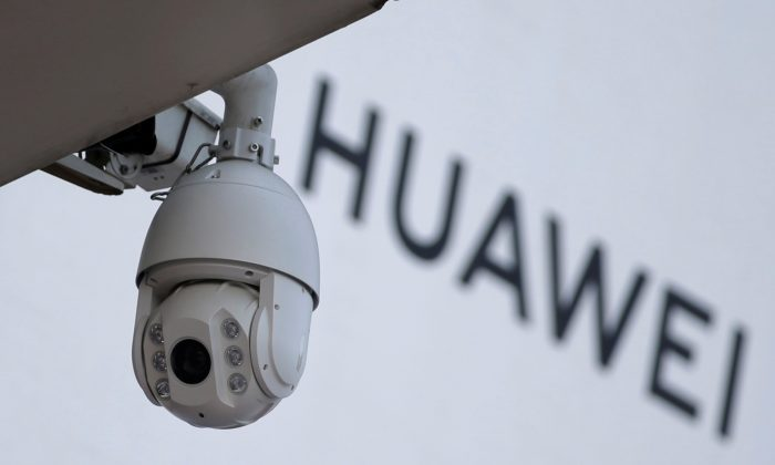 A surveillance camera next to a sign of Huawei outside a shopping mall in Beijing on Jan. 29, 2019. (Jason Lee/Reuters)