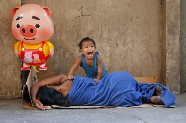 With a balloon shaped as an earth pig, a homeless child reacts