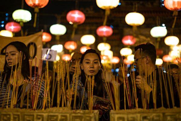 Worshippers burn incense and pray at the Wong Tai Sin Temple