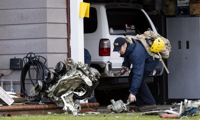 A National Transportation Safety Board worker takes a photo of an engine that came to rest against a house on Crestknoll Dr. in Yorba Linda, Calif., on Feb. 4, 2019. (Paul Bersebach/The Orange County Register via AP)