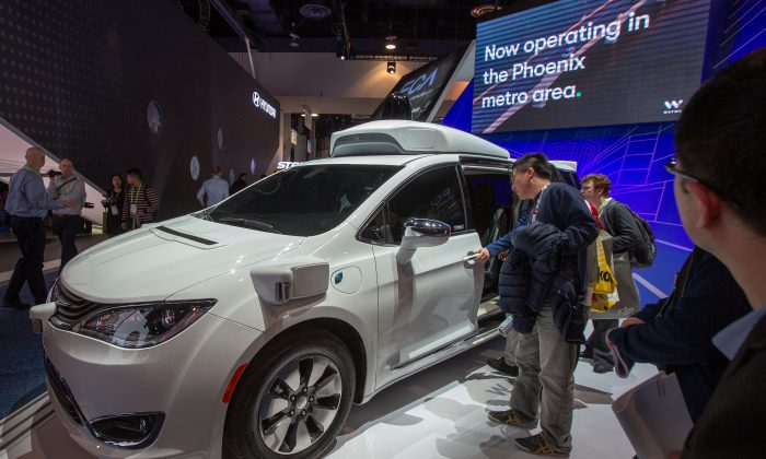 People look at a Waymo self-driving car during CES 2019 in Las Vegas on Jan. 9, 2019. (DAVID MCNEW/AFP/Getty Images)