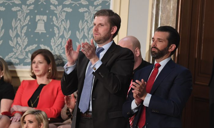 Eric Trump (L) and Donald Trump, Jr., applaud as their father President Donald Trump delivers the State of the Union address before a Joint Session of Congress in Washington on Feb. 5, 2019. (Saul Loeb/AFP/Getty Images)
