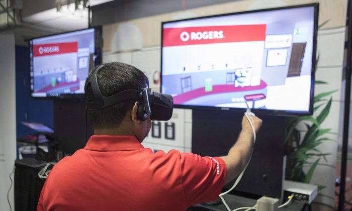 A Rogers employee wears virtual reality (VR) goggles at a stall promoting VR retail over5G wireless networks, at a press event in Toronto, Canada on April 16, 2018. (The Canadian Press/Chris Young)