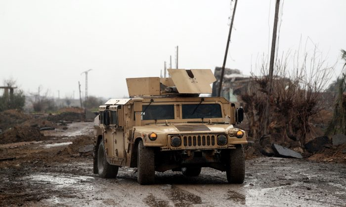 Syrian Democratic Forces (SDF) vehicles make their way on a dirt road on Jan. 28, 2019, in the town of Sousa, in Syria's eastern province of Deir Ezzor. (DELIL SOULEIMAN/AFP/Getty Images)