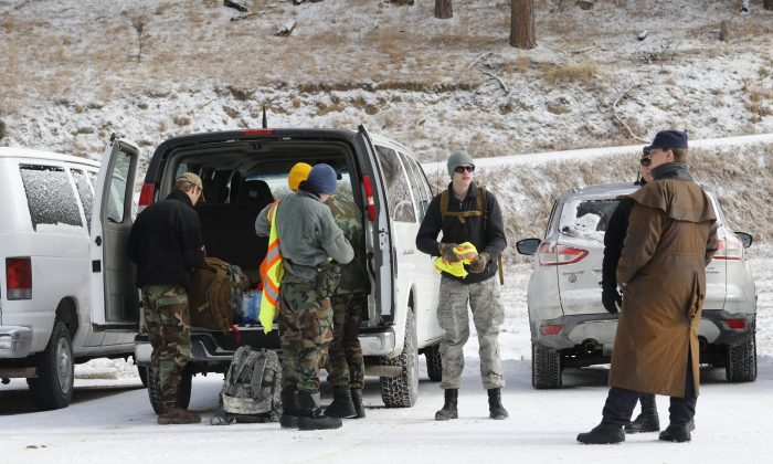 A dog helps search for Serenity Dennard, 9, on Feb. 4, 2019, near Rockerville, S.D. Authorities say that the girl ran away from staff at a residential youth home. (Arielle Zionts/Rapid City Journal via AP)