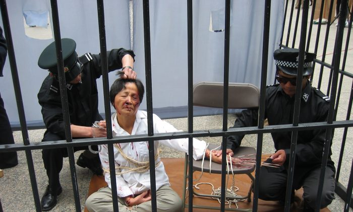 A reenactment of a Falun Gong practitioner being tortured by police in a detention center. (Minghui.tv)