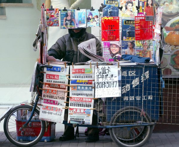 A man arranges newspaper at his newsstand in Shanghai.