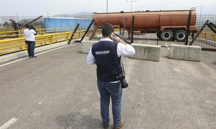 An immigration official observes a fuel tanker, cargo trailers, and makeshift fencing, used as barricades by Venezuelan authorities attempting to block humanitarian aid entering from Colombia on the Tienditas International Bridge that links the two countries as seen from the outskirts of Cucuta, Colombia, on Feb. 6, 2019. (AP Photo/Fernando Vergara)