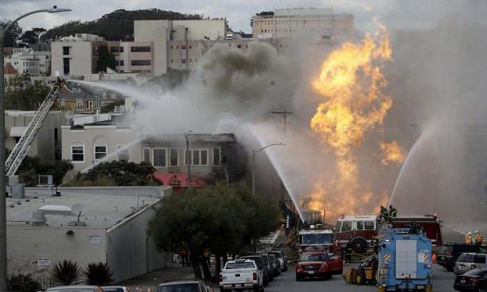 San Francisco firefighters battle a fire on Geary Boulevard in San Francisco, on Feb. 6, 2019. A gas explosion in a San Francisco neighborhood shot flames high into the air and was burning four buildings as utility crews scrambled to shut off the flow of gas. (Jeff Chiu/AP Photo)