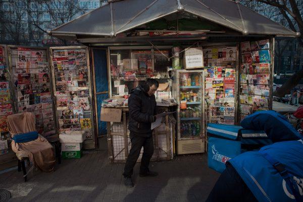 A man reads a newspaper in Beijing.