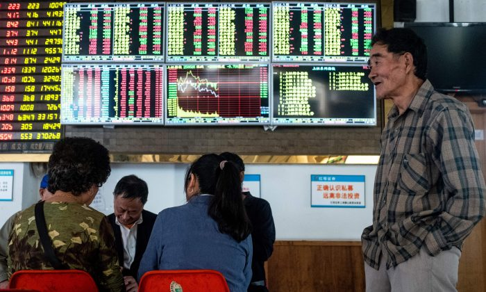 An investor looks at an electronic board showing stock information at a brokerage house in Shanghai on October 15, 2018. (Photo by JOHANNES EISELE/AFP/Getty Images)