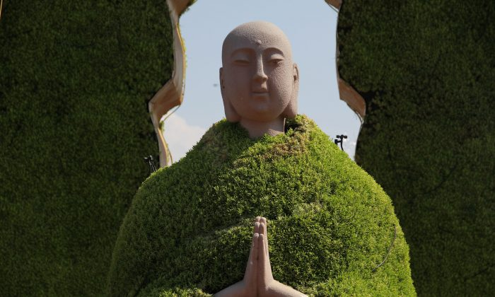 """A sculpture of Monk Tang (also known as Tang Xuanzang in the Chinese novel """"Journey to the West"""") wearing a """"green coat"""" made up of green plants at Dayanta in Xi'an, Shaanxi Province of China on July 15, 2014. (VCG/VCG via Getty Images)"""