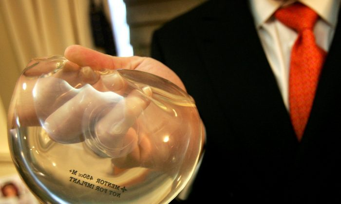 Dr. Brad Jacobs holds up a silicone implant gel (L) and a saline implant gel (R) inside of his office in New York City, on Nov. 21, 2006. (Spencer Platt/Getty Images)