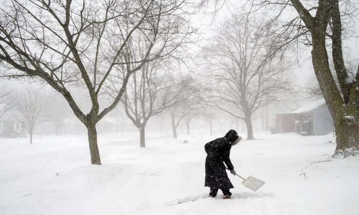 Abby Morin shovels a path as snow continues to fall in Grand Rapids, Mich., on Feb. 8, 2019. (Neil Blake/The Grand Rapids Press via AP)