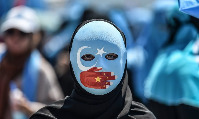 A demonstrator wearing a mask painted with the colors of the flag of East Turkestan—how some separatist Uyghurs refer to the region of Xinjiang—and a hand bearing the colors of the Chinese Communist Party flag, attends a protest denouncing China's treatment of ethnic Uyghur Muslims, in front of the Chinese consulate in Istanbul, on July 5, 2018. (OZAN KOSE/AFP/Getty Images)