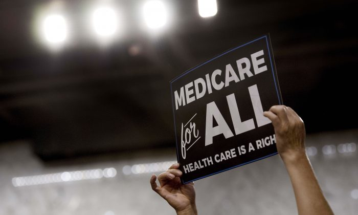 A member of the audience holds up a placard as US Sen. Bernie Sanders, (I-Vt.), discusses Medicare for All legislation on Capitol Hill in Washington on Sept. 13, 2017.  JIM WATSON/AFP/Getty Images