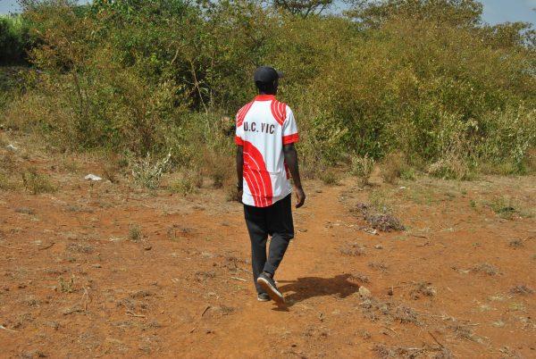 man walking towards bushes