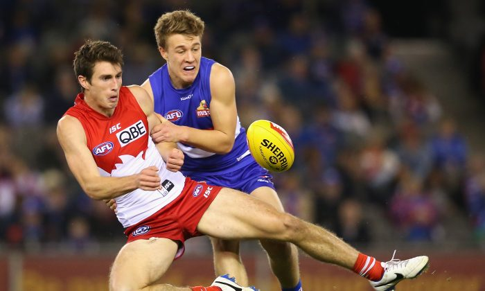 Dean Towers of the Swans handballs whilst being tackled by Jackson Macrae of the Bulldogs during the round 22 AFL match between the Western Bulldogs and the Sydney Swans at Etihad Stadium on Aug. 24, 2014 in Melbourne, Australia.  (Quinn Rooney/Getty Images)