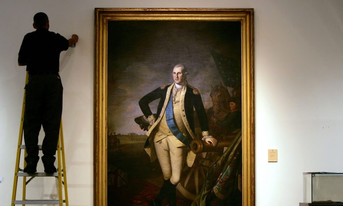 A worker uses a ladder to work near a Charles Willson Peale portrait of founding US President George Washington, shown here as a General after the Battle of Princeton, at Christie's auction house in New York on Jan. 17, 2006. (Spencer Platt/Getty Images)