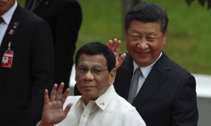 Chinese leader President Xi Jinping (R) and Philippines' President Rodrigo Duterte waves to members of the media after inspecting the honor guard during a welcoming ceremony at the Malacanang Palace in Manila on Nov. 20, 2018. (Ted Aljibe/AFP/Getty Images)